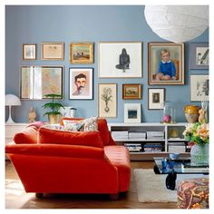 Duck egg blue gallery wall and bright red - orange sofa