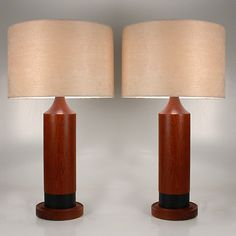 A pair of simple mid-century modern lamps, cylindrical, deep red brown teak accented with black bands at the base. Topped with contemporary shades. Image © Eclectisaurus. Visit our shop at 249 Gerrard St E, Toronto. 416-934-9009 www.eclectisaurus.com