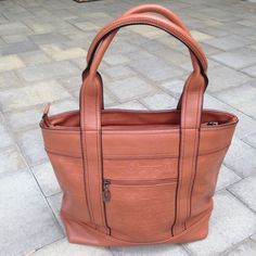 "Leather look tote bag Great quality leather look-alike tote bag. Plenty of zippered storage. Classic embossed design. Color: cognac with black piping. 12""H x 15 1/2"" W (not including handles). Condition: NEW Bags Totes"