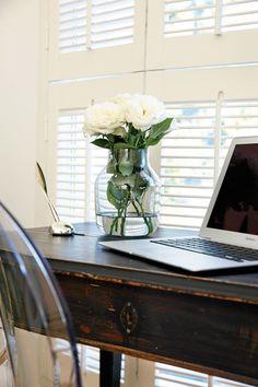 1800-luvun kirjoituspöytä olohuoneen päädyssä on ostettu Sea Antiques -liikkeestä. Kartellin väritön Ghost-tuoli keventää tumman pöydän ilmettä. Valkoiset ruusut ovat Muuton maljakossa.