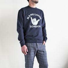 """英国ブランドYMCの""""Hang Loose London!"""" スウェット。 Hang Looseとは、""""ゆったりと行こう!""""、""""気楽に人生を楽しもう!""""というニュアンスを持つ言葉。カラーはネイビーにホワイトのグラフィックプリント。素材は、プレミアムコットンを使用したループバック・ジャージィ。厚地過ぎないミディアムウェイトのスウェットは、季節の変わり目にとても便利なアイテムです。軽い着心地のよさも魅力。"""