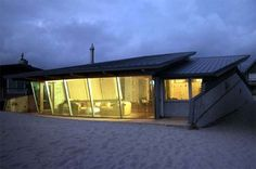I'm not sure that this counts as a tiny home but this place is very sweet!   Small Beach House Design with Sloping Roof.