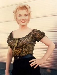 Marilyn Monroe resplendent in a scoop-neck top, pencil skirt, and sassy pose, Monroe gets hippy (and lippy) outside a film trailer in 1957.