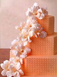 Orange wedding cake with lovely, cascading sugary flowers. Pretty.