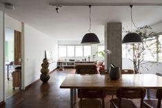 Para iluminar a sala de jantar os arquitetos Márcio Bariani e Alessandro Muzi escolheram pendentes de aspecto industrial, que proporcionam uma luz focada, mas suave. As luminárias (Reka) são presas em um trilho fixado ao teto, que permite flexibilidade em eventual mudança do layout ou mesmo no caso de troca da mesa de jantar. No mesmo trilho foram instalados spots orientáveis (também Reka), com luz para destaque de peças de decoração, como a escultura cerâmica (Kimi Nii)