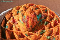 M&M Cream Cheese Bundt Cake      1½ cups butter (3 sticks)- softened     1 (8 ounce) package cream cheese- softened     2½ cups white sugar     1 T vanilla     1 t almond extract (optional)     6 eggs at room temperature     3 cups cake flour     ½ t baking powder     ½ t fine sea salt     1 cup baking M&Ms     ⅓ cup mini chocolate chips  oven to 325 F