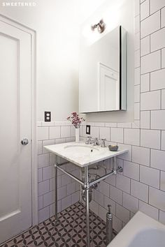 Washington Heights Bathroom features frameless, wall-mounted medicine cabinet, vanity lighting fixture, and open sink console from Signature Hardware.