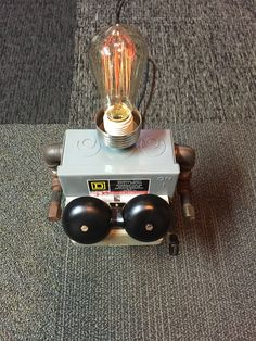 "Robot Lamp, Robo 6 ""Hello Boys"" Head is a Zero Hour Bomb Company (ZEBCO) fishing reel cover, re-used socket and new Edison bulb, Body is a Square D electrical disconnect box, arms are pipe fittings, chest is telephone outdoor bell system, has new electrical box and dimmer on the back."