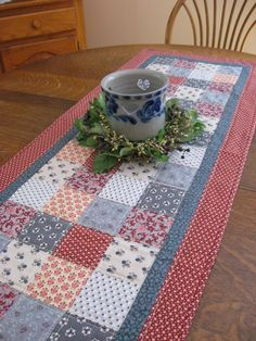 A beautiful country quilted table runner, measuring 49 x18. This runner would make the perfect accent to your dining room, country kitchen or anywhere in your home and just perfect for summer holiday decorating. Runner has been created in a block pattern within the center of the runner, with an inset center border and wider outer border. The runner features an assortment of country themed fabric prints and colors featuring red, rust blue, gray, and cream. The outer border features a deep red…