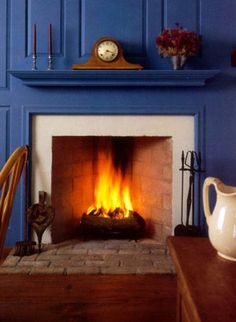A classic fireplace with blue painted raised panel walls & mantel- great contrast to the warmth of the roaring fire.