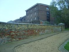 The remaining wall of the Royal Marine barracks, Chatham. You can see where the wall had later repair work done, and was heightened, using different colour bricks. The big building behind the wall is one of the storehouses in the Historic Dockyard. (Picture taken by me)