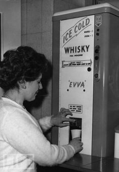 """Automatic Whisky, 1960  At the Second Automatic Vending Exhibition in London, a woman helps herself to a vending machine-mixed whisky and soda."""