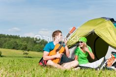 Stock Photo : Camping couple playing guitar by tent countryside