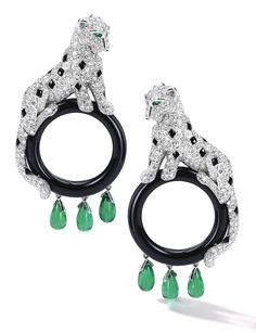 Pair of Diamond, Emerald and Onyx Ear Clips, 'Panthère', Cartier Each designed as a panther pavé-set with circular-cut diamonds accented with onyx spots and emerald eyes, resting on an onyx hoop, suspending three drop-shaped emeralds, mounted in 18 karat white gold, signed Cartier and numbered.