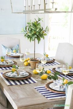 A beautiful summer tablescape inspired by the Amalfi Coast in Italy. Lemons, navy blue and white stripes, linen chairs, reclaimed wood table and wine!
