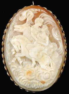 jewelry, , A large carved shell cameo brooch. Vertical oval scene showing two lovers on separate horses in cream color with orange to cream ...
