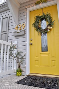 ENTRYWAY:: DOOR COLOR, ACCENTS, FRAMEWORK  ~~ Bright sunshine yellow livens up neutral house exterior color. Smart that they picked it up again in the house address numbers. Wreath (especially gold ornaments) lights, greenery are homey, inviting. Could easily switch up wreaths for different seasons.