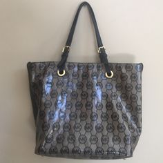 Michael Kors Bag! Michael Kors. Tan/ Black with gold hardware. Has a shiny exterior. Has black interior with pockets as well as zipper pocket. Only minor wear on hardware. In really great condition!! Michael Kors Bags Totes