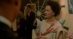 Pollock (2000) - Amy Madigan as Peggy Guggenheim wearing a short-sleeved dress embellished with a beaded lobster and mismatched earrings.  The costumes were designed by David C. Robinson.  The dress is a homage to the iconic lobster dress designed by Elsa Schiaparelli and Salvador Dalì in 1937.The mismatched earrings were actually worn by Guggenheim at the opening of her museum-gallery Art of This Century in New York in 1942. The gold one is a miniature mobile designed by Alexander Calder…