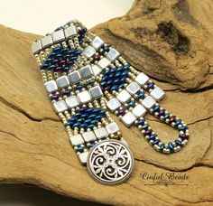 A very stylish beaded bracelet using the popular two hole beads Super Duos and Czechmate Tiles. These are both pressed glass beads made in the Czech Republic. The design has a bit of a Southwest feel to it, but yet could fit into the contemporary category as well. A diamond shaped pattern of bright metallic blue iris Super Duos alternates with rows of silver tile beads. Toho permanent finish galvanized silver seed beads have been used to connect it all. The blue iris beads really jump out…