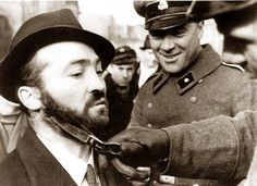 """Men of the SS Totenkopfverbande smile  while cutting the beard of a Polish Jew. While not all German soldiers, or even all SS, were anti-Semitic, it was an absolute prerequisite for admission into the Totenkopf Division, whose members were infamous for their brutality and hatred of Jews and other """"untermenschen"""", or """"subhumans""""."""