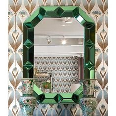 In this vintage-inspired wall mirror, a long octagonal form complements the dynamic angularity and dimensions created by beveled patterns in the frame.