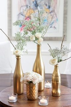 Gold painted bottles and jars with simple white flowers as centerpieces #wedding #gold #goldwedding #diywedding #tablecenterpieces