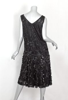 Sequined tulle dress, c.1925 The unstructured dress is comfortable and effortless to wear. The black rayon lining is attached around the neckline and armholes. The dress is cut straight to the hipline, where it is attached to a bias-cut circular skirt.  The sophisticated black-on-black design is punctuated with bursts of glitter from a textured assortment of sequins and beads: large diamond-shaped paillettes, sequins, and glass beads.   Back 2