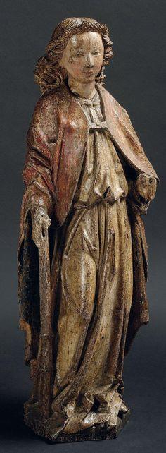 BEL ANGE en chêne sculpté en ronde bosse et polychromé. Debout, il est vêtu d'une tunique blousant à la taille et d'une chape dont le rabat se termine par un pompon dans le dos; visage aux formes pleines encadré par une chevelure bouclée et retenue par un diadème. Brabant ou Allemagne du Nord, XVe siècle.