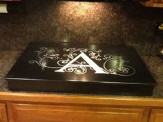 I love my newly hand painted stove top cover from www.centerstagekitchens.com. It's custom ordered to size and hides my ugly burners.