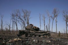 A fighter with the separatist self-proclaimed Donetsk People's Republic army looks at a destroyed Ukrainian army tank near the town of Debaltseve February 22, 2015. REUTERS/Baz Ratner