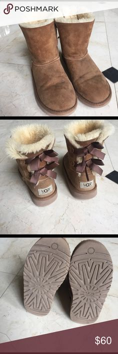 Tan bailey bow uggs These uggs are perfect for any weather and make an adorable hint to any outfit! The uggs are lightly worn but are being sold for a fair price. They have dark brown ribbons on the back to add a more elegant look. UGG Shoes Boots