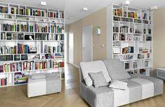 Dwa duże regały, zrobione na wymiar zmalowanej płyty MDF, mieszczą domową biblioteczkę. Dwukolorowe, biało-szare meble wypoczynkowe (z firmy Agata) zdradzają zamiłowanie gospodarzy do spokojnych barw.