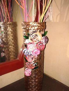 jarrón hecho con tres tarros metálicos y forrado con papel periódico decorado con flores de papel.