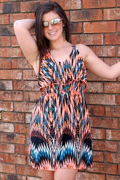 Bright neon printed racerback dress with a cinched waist. Taylor is wearing a size small. (100% Polyester)