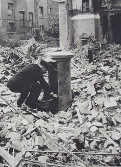 Postman emptying pillar mailbox in London after a bombing raid in World War II... perseverance.