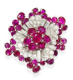 A ruby and diamond clip brooch, by Cartier, circa 1950 The abstract flowerhead set with brilliant and baguette-cut diamonds and circular and oval-cut rubies, diamonds approximately 4.40 carats total, signed Cartier London, maker's case, length 4.5cm