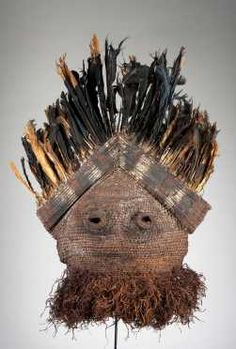 """A fine Binji woven fiber mask. -  People: Binji, DR Congo; H: 30"""" The mask of typical form, found among the Binji and Dinga in the west, to the Kete-Bushong in the north, and as far as some of the Luba groups in the east; in the form of a woven plaited hood, with clearly indicated eyes, the top with lashed split cane painted in red, black, and white, The reverse with plaited band and applied abrus seeds, and crowned with feathers."""