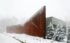 The curved wall carves a modest entry court that amplifies the sound of the stream running parallel to the house | A House In The Woods | William Reue Architecture