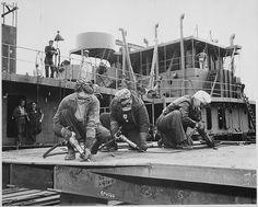 Chippers in a Shipyard [Shipbuilding. Three Women Working], 1942. - WWII propaganda photo USA, women war workers