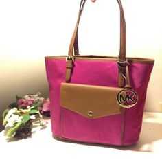 """NWT Michael Kors Jet Set Fushia & brown Brand: Michael KORS Material: Patent Leather Print/Solid: Solid Size: Medium NWT Michael Kors Jet Set Fushia Brown Medium Multifunction Pocket Purse Tote Bag  100% Authentic Michael Kors Brand New with Tags  Color: Fushia Nylon with Luggage Leather trim.  Accented with golden tone hardware.  Signature MK Fob in front.  Interior features a large center zip pocket, 4 multifunction slip pockets, 1 zip pocket.   13"""" (L)x 9""""(H) x 5"""" (W), 7"""" Strap drop…"""