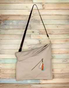 This ivory color leather crossbody bag (or messenger bag) can be used in several ways: completely folded or in its full capacity fashion (unfolded). Should you need more room to carry stuff?, you can change the strap and hook it to the upper rings to gain capacity.   COLORS & MATERIALS Hand-made in genuine ivory cow leather. This kind of leather is very soft and supple. It has three leather tassels in shades of off-white, orange and aqua and an adjustable leather strap in brown, with opaque…