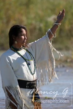 A Native American Indian woman worshiping the sun while standing in the river in South Dakota / Nancy G Photography