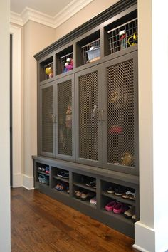 Fantastic mudroom features gray built-in lockers boasting cubbies filled with vintage metal locker bins and metal grill mesh doors on lockers over stacked shoe shelves.