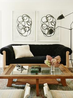 Tufted black and wood sofa, abstract wall art, and wooden and glass coffee table with antique decor.