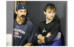George Parros (left) and goalie Peter Budaj watch from a door leading to the dressing room as their teammates take part in a scrimmage at th. Of Montreal, Montreal Canadiens, Hockey Players, Dressing Room, Watch, Sports, Hs Sports, Bracelet Watch, Clocks