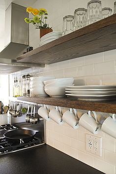 """...The supports are long steel bars that go through the shelves and into the studs in the wall. We predrilled holes for them before we tiled. We used oak planks seamed together to make a solid wood shelf."" I love the hanging white coffee mugs! It would be cute to add a touch of color with the dishes here and there."
