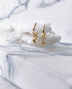 Gorgeous gold star and moon ear hoops hanging on a white coral. Beautiful hoop earrings with star moon design. Lovely jewellery display. Perfect for stacking for the modern minimalist - CLICK TO SHOP CELESTIAL STAR MOON SMALL EAR HOOPS NOW