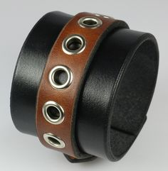 """Who says brown and black don't match? This amazing men's leather cuff has it all: Solid buckle with leather strap keeper, two-tone full grain leather, and just the right amount of eyelets. 2"""" wide bla"""