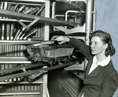 May 22, 1938: Mary J. Coyle loaded a book cart deep in the stacks of the Boston Public Library to carry the book freight to the delivery desk using the library's interior electric railway system. Tiny cars with a capacity of about a dozen books each ran constantly from the depths of the stacks to the circulation desk in response to slips from patrons which were electrically dispatched from the desk. Boston Globe Archives |
